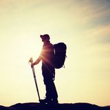 Tourist in windcheater with sporty trecking  poles in hands stand on rocky view point. Royalty Free Stock Images