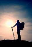 Tourist in windcheater with sporty trecking  poles in hands stand on rocky view point. Stock Image