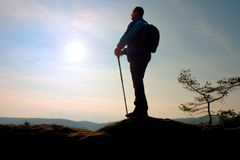 Tourist in windcheater with sporty trecking  poles in hands stand on rocky view point. Royalty Free Stock Photos
