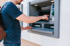 The tourist withdraws money from the ATM for further travel. Finance, credit card, withdrawal of money. Life style. The tourist withdraws money from the ATM for Royalty Free Stock Photography
