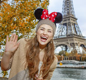 Tourist woman шт Minnie Mouse Ears in Paris handwaving. Perfect autumn holidays in Disneyland and Paris. Portrait of happy tourist woman wearing Minnie royalty free stock photo