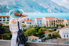 Tourist woman admiring view of colorful tranquil village Assos on morning. Young stylish female model wearing blue stock image
