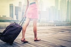 Tourist or woman adventure with luggage in Singapore. In front of business buildings and offices, there is a bright spot in the center for a any text Royalty Free Stock Photo