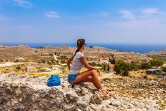 Tourist woman in ancient Archangelos castle in scenic old town on Rhodes island, Dodecanese, Greece. Beautiful picturesque white. Houses with flowers. Famous royalty free stock photo