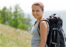 Woman with backpack on green hill Stock Photo