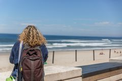 A tourist woman with a backpack on her back, placidly observes a calm sea on a beach, on a sunny day. A tourist woman with a backpack on her back, placidly stock photo