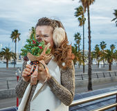 Tourist woman in Barcelona hiding behind a little Christmas tree Stock Images
