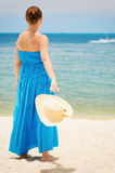 Woman in blue dress throws hat on the beach Royalty Free Stock Image