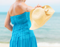 Woman in blue dress throws hat on the beach Stock Photo