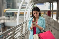 Tourist woman browse internet from smartphone. Beautiful Asian Tourist woman browsing store map by 4g internet on smartphone to find shopping and travel location Stock Photography