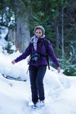 Tourist woman with camera in the snowy forest Royalty Free Stock Images