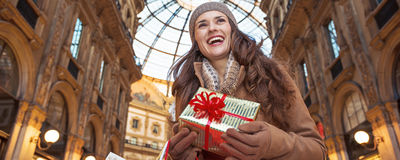 Tourist woman with Christmas gift in Milan looking into distance Royalty Free Stock Images