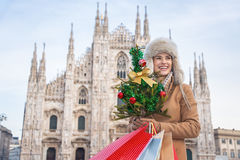 Tourist woman with Christmas tree and shopping bags in Milan. Fun Christmas trip to Milan, Italy. Portrait of happy young tourist woman in the front of Cathedral royalty free stock photos