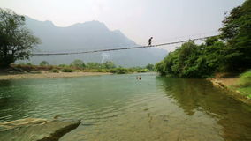 Tourist woman crossing dangerous bamboo suspension bridge, laos stock video
