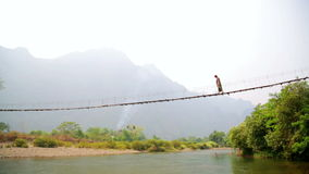 Tourist woman crossing dangerous bamboo suspension bridge,laos stock footage