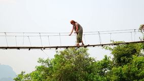 Tourist woman crossing dangerous bamboo suspension bridge,laos stock video footage