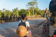 Tourist woman cycling around Angkor temple, Cambodia. Angkor Thom main gate Buddha face sculpure ruins in the jungle. Eco friendly. Tourism traveling royalty free stock photo