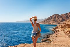 Tourist woman in Dahab near Blue Hole at the Red Sea coast. Famous travel destionation in desert. Sharm el Sheik, Dahab, Sinai. Peninsula, Egypt stock photo