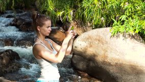 Tourist woman doing photo wild nature on mobile phone while climbing in mountain waterfall in rainforest. Traveling. Woman tourist shooting video on smartphone stock video footage