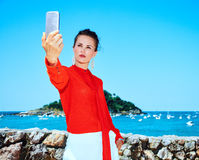 Tourist woman in Donostia, Spain with smartphone taking selfie Royalty Free Stock Photography