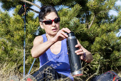 Tourist woman drinking tea in a forest Stock Images