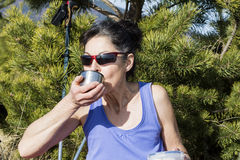 Tourist woman drinking tea in a forest Royalty Free Stock Photo