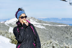 Tourist woman eating apple  in the winter mountain Stock Image