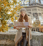 Tourist woman on embankment near Eiffel tower looking at map. Autumn getaways in Paris. young tourist woman on embankment near Eiffel tower in Paris, France Stock Images