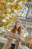 Tourist woman on embankment near Eiffel tower looking at map. Autumn getaways in Paris. young tourist woman on embankment near Eiffel tower in Paris, France Royalty Free Stock Photo