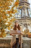 Tourist woman on embankment near Eiffel tower looking at map. Autumn getaways in Paris. young tourist woman on embankment near Eiffel tower in Paris, France Stock Photos
