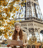 Tourist woman on embankment near Eiffel tower in Paris with map. Autumn getaways in Paris. Portrait of smiling young tourist woman on embankment near Eiffel Stock Photography