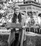 Tourist woman on embankment near Eiffel tower in Paris with map. Autumn getaways in Paris. Portrait of smiling young tourist woman on embankment near Eiffel Stock Image