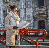 Tourist woman in front of Duomo in Milan, Italy looking at map Royalty Free Stock Photos