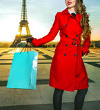 Tourist woman in front of Eiffel tower holding shopping bag. Bright in Paris. smiling elegant tourist woman in red coat in the front of Eiffel tower in Paris Stock Images