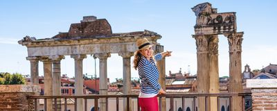 Tourist woman in front of Roman Forum pointing at something. Roman Holiday. Full length portrait of smiling young tourist woman in the front of Roman Forum in Stock Image