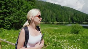 Tourist woman goes to a picturesque place in the background of meadows, mountains and sky. Tourism and active lifestyle