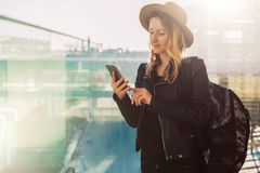 Tourist woman in hat, with backpack stands at airport, uses smartphone. Girl checks email, chatting, browsing internet. Young tourist woman in hat, with Stock Image