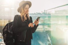 Tourist woman in hat, with backpack stands at airport, uses smartphone. Girl checks email, chatting, browsing internet. Young tourist woman in hat, with Stock Images