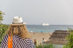A tourist woman with a hat, placidly observes a beach with people. A tourist woman with a hat, placidly observes a nice beach with people stock photo