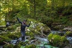 Hiker woman in a river. Tourist woman hiking into the wilderness by a river Stock Photography