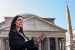 Tourist woman hold a map looking for directions. And wondered.  Rome Pantheon in Italy as background Stock Photos