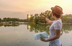 Tourist woman holding map and pointing to direction Royalty Free Stock Photo