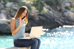 Tourist woman on holidays enjoying online with a laptop. On the beach with the sea in the background Royalty Free Stock Photos
