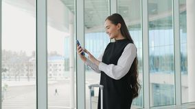 Tourist woman in international airport terminal with luggage using smart phone. Voice recognition text message command. Tourist woman in international airport stock footage