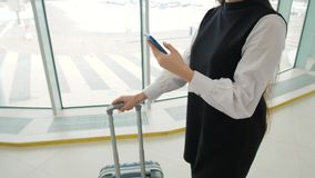 Tourist woman in international airport terminal with luggage using smart phone. Voice recognition text message command. Tourist woman in international airport stock video