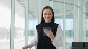 Tourist woman in international airport terminal with luggage using smart phone. Voice recognition text message command. Tourist woman in international airport stock video footage