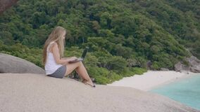 Tourist Woman With Laptop. Tourist woman on holidays enjoying online with a laptop on top of the mountain with view over white sand beach with turquoise sea stock footage