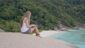Tourist Woman With Laptop. Tourist woman on holidays enjoying online with a laptop on top of the mountain with view over white sand beach and lagoon. Vacation stock video footage