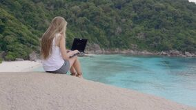 Tourist Woman With Laptop. Tourist woman on holidays enjoying online with a laptop on top of the mountain with view over white sand beach and lagoon. Vacation stock footage