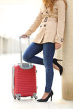 Tourist woman legs waiting with a suitcase in an airport Royalty Free Stock Image